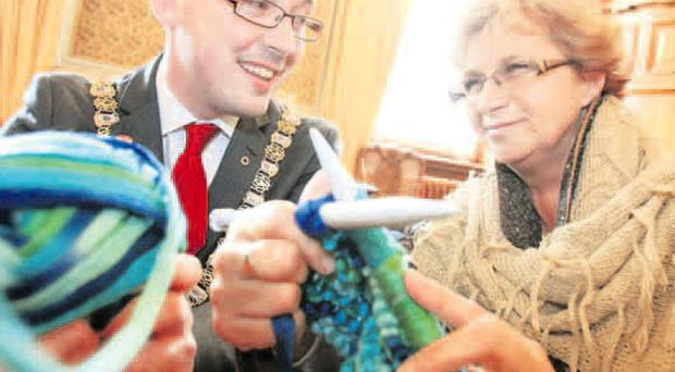 Lord Mayor Niall Ó Donnghaile is given a helping hand by knitter Maggie Jackson yesterday