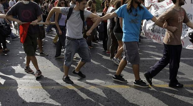 University students take part in a protest outside parliament in Athens (AP)