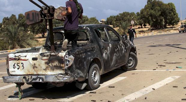 Revolutionary fighters on armed vehicles guard the northern road leading out of the western main square in Sirte (AP)