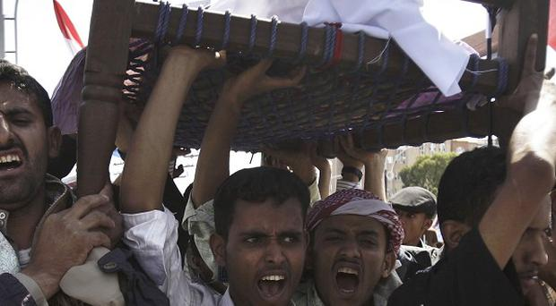 Anti-government protesters in Sanaa carry the body of a Yemeni man who was killed in recent clashes with security forces