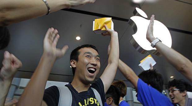 A customer cheers with staff at the new Apple store in Hong Kong