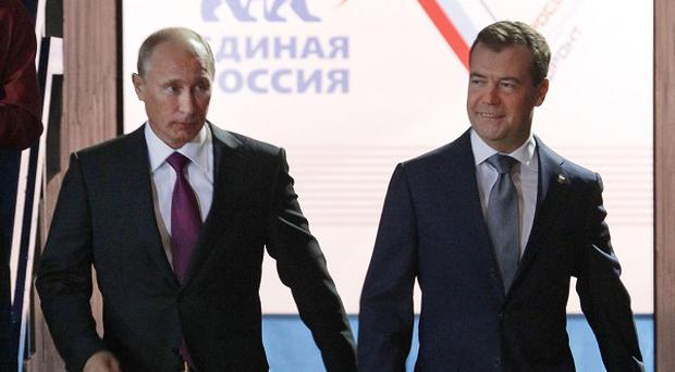 Russian president Dmitry Medvedev, right, and PM Vladimir Putin arrive to attend a United Russia party congress in Moscow (AP)