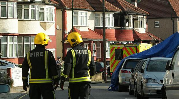 Emergency workers close to a semi-detached property in Neasden where six members of the same family died in a fire