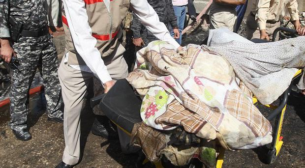 A body is taken from the scene of a bomb attack in Karbala (AP)