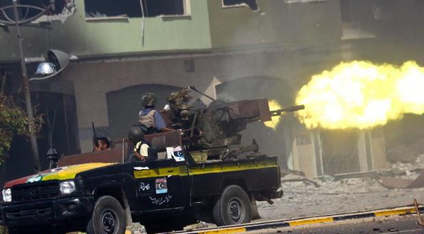 Fighters from Libya's ruling National Transitional Council fire at pro-Gaddafi forces during heavy battles in Sirte (AP)