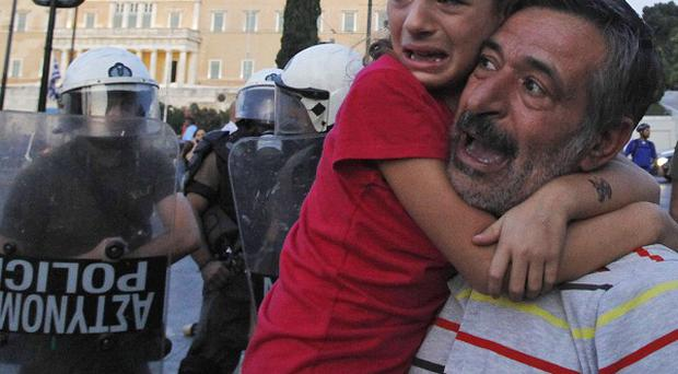 A father holds his daughter during protests in front of the Greek parliament in Athens (AP)