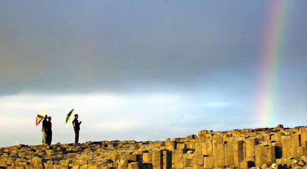 Tourists stop to admire the iconic landscape of the Giant's Causeway on the north Antrim coast.