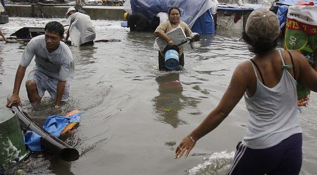 Residents evacuate to higher grounds in Navotas, north of Manila, Philippines (AP)