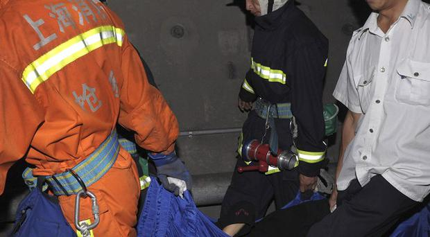 Rescue workers carry an injured passenger from the two train subway crash in Shangha(AP)