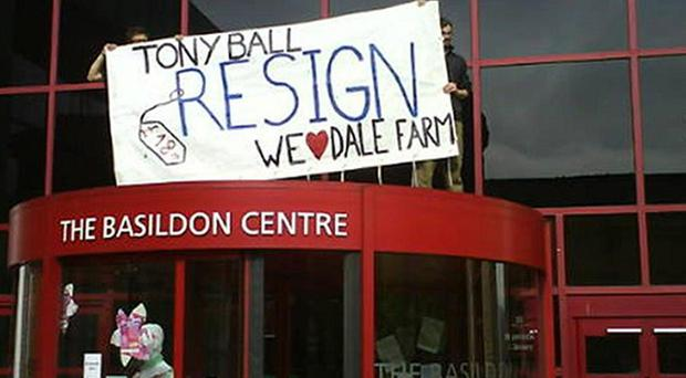 Activists have scaled the front of council offices in Basildon in protest at plans to clear Dale Farm