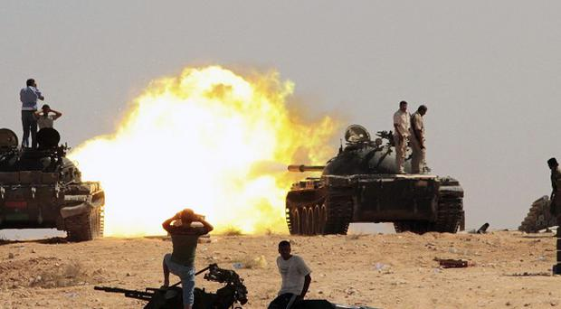 Revolutionary fighters fire from tanks towards Gaddafi troop positions in Sirte(AP)