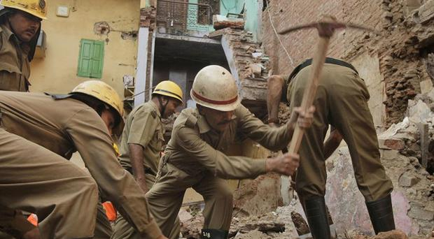 Rescue workers dig rubble from a collapsed building in the Old Delhi area of New Delhi (AP)