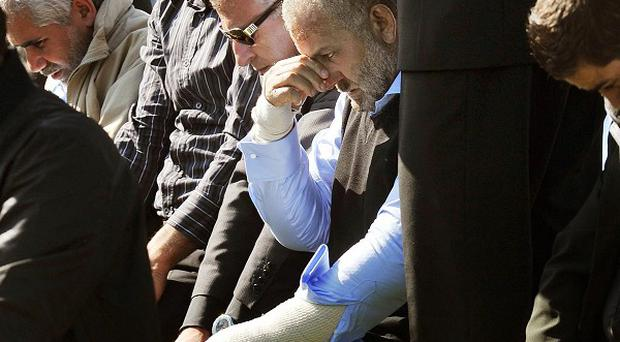 Bassam Kua, centre, with bandaged arms, mourns for his wife and five children who were killed in a house fire