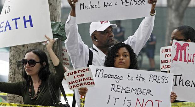 Michael Jackson fans hold signs outside court on Wednesday (AP)