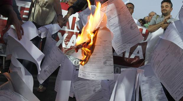 Greek demonstrators burn copies of emergency tax notices during a protest by the Communist-backed labor union in Athens (AP)