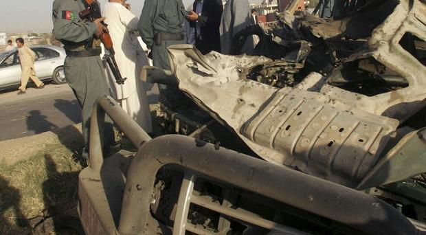 Security forces investigate at the scene of an explosion in Herat, western Afghanistan (AP)