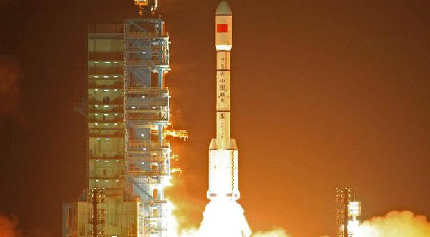 A rocket carrying the Tiangong-1 space module blasts off from the Jiuquan launch centre (AP)