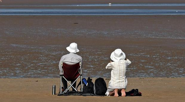 A couple enjoy the sunshine on Brancaster beach in north Norfolk