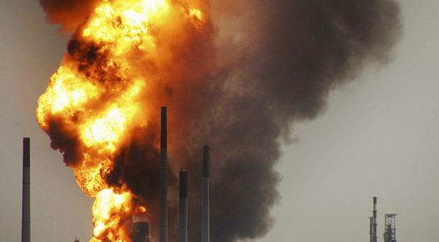 Smoke and flames rise from the Royal Dutch Shell's Pulau Bukom offshore petroleum complex in Singapore (AP)