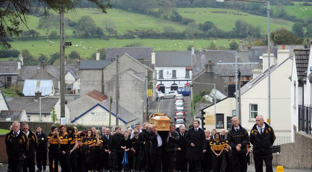 The cortege of Karen Coyles, flanked by members of Ballycastle GAA camogie team, makes its way to the chapel in Ballycastle during her funeral in the Co. Antrim town yesterday
