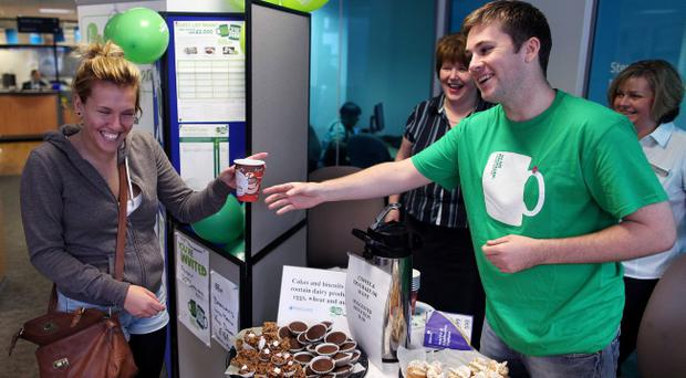 Macmillan Coffee Day at Barclays Bank in Castle Place, Belfast yesterday. Katie Chedder gets a coffee from Cathal Cullen