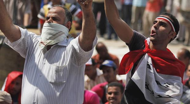 Egyptian demonstrators chant slogans as they attend a protest at Tahrir Square in Cairo (AP)