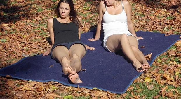 Danish tourists Camilla Karbo, 29, and Katrina Karbo, 28, enjoy the hot sunshine amid the autumn leaves in Battersea Park, south London
