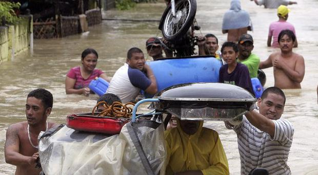 Residents evacuate to safer grounds with their belongings as massive flooding continues for the second day in the Philippines (AP)
