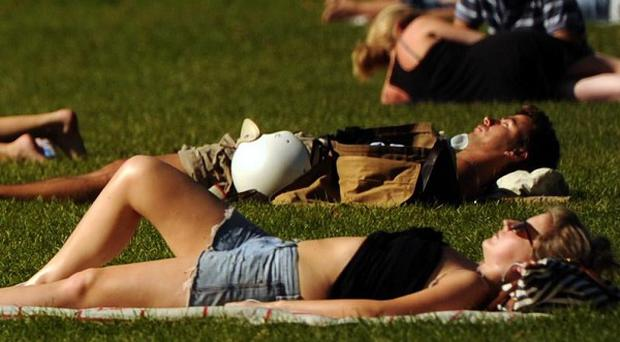 Members of the public enjoy the unseasonably warm weather on Clapham Common, London