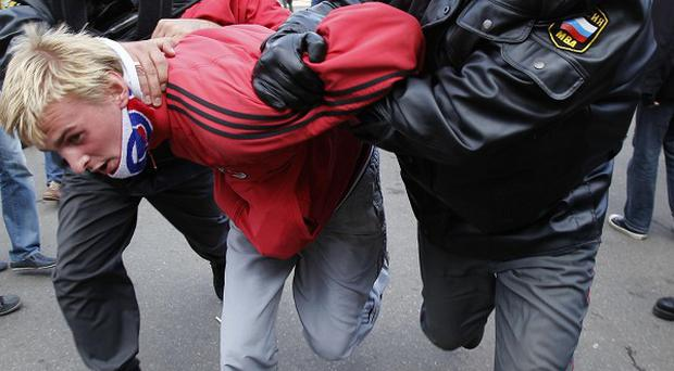 Russian police officers detain an anti-gay protester during a gay pride rally in central Moscow (AP)