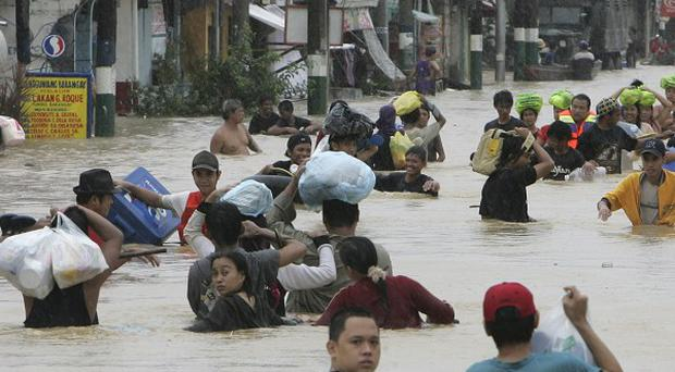 Residents evacuate to safer grounds amid flooded streets after two tyhoons hit the Philippines (AP)