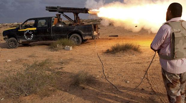 Revolutionary forces have completely surrounded Muammar Gaddafi's hometown of Sirte, a Libyan commander said (AP)