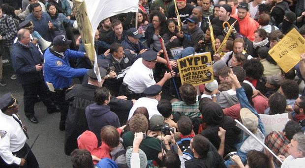 Police enter the crowd to make arrests as a large group of protesters march across the Brooklyn Bridge in New York (AP)