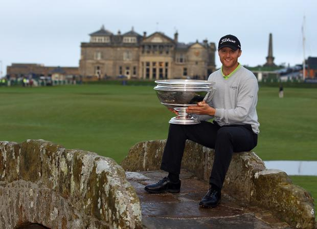 Ulsterman Michael Hoey stands aloft the Swilken Bridge at the 18th hole at St Andrew's to show off the Alfred Dunhill Links trophy which he won on Sunday