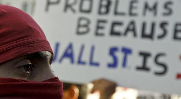 An Anti-Wall Street demonstrator marches in downtown Los Angeles (AP)