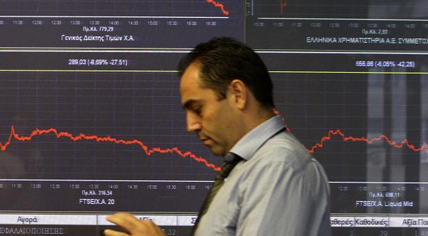 A man in front of a chart showing share prices at the Greek Stock Exchange in Athens (AP)