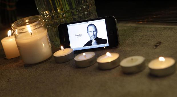 An iPhone displays an image of Steve Jobs as it sits with a memorial to the Apple founder and former CEO outside an Apple Store, Wednesday, Oct. 5, 2011 in New York