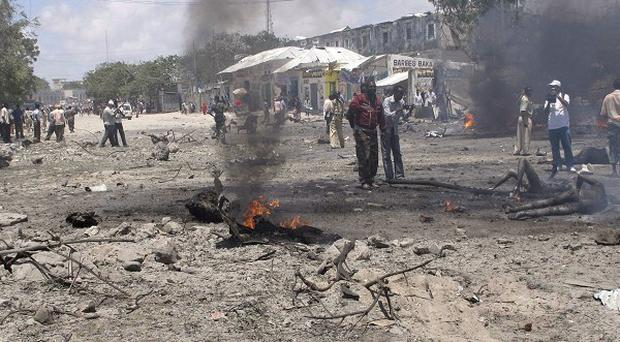 A Somali soldier keeps guard near the scene of an explosion in Mogadishu (AP)