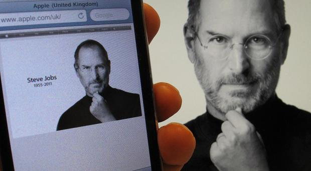 An iPhone and an iMac show a picture of Steve Jobs, who has died aged 56