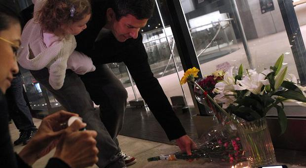 People leave flowers and candles at a memorial to Steve Jobs outside an Apple store in New York
