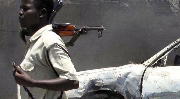 A Somali soldier keeps guard at the scene of an explosion in Mogadishu