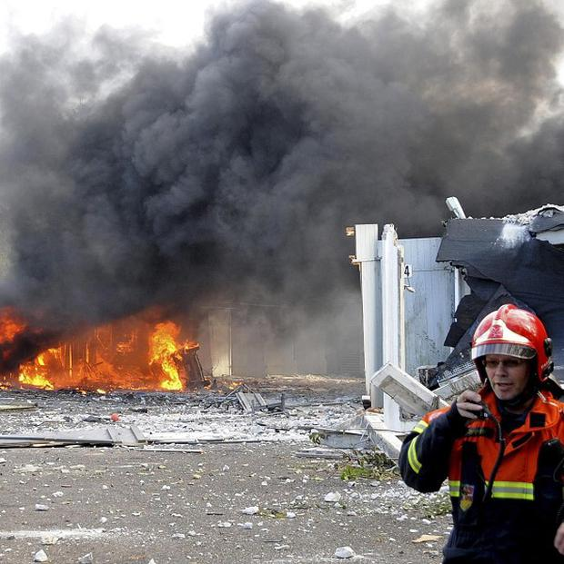 An emergency worker assists at the site of a warehouse fire following a series of violent explosions in Denmark (AP)