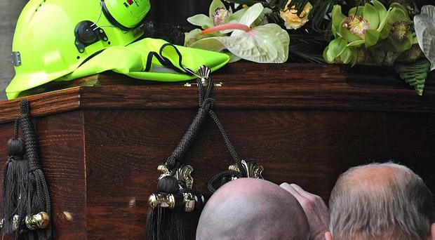 A miner's helmet and yellow vest placed on top of the coffin of Gerry Gibson at his funeral service