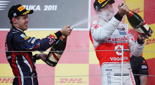 SUZUKA, JAPAN - OCTOBER 09: (L-R) Third placed Sebastian Vettel of Germany and Red Bull Racing celebrates on the podium with race winner Jenson Button of Great Britain and McLaren following the Japanese Formula One Grand Prix at Suzuka Circuit on October 9, 2011 in Suzuka, Japan. (Photo by Mark Thompson/Getty Images)