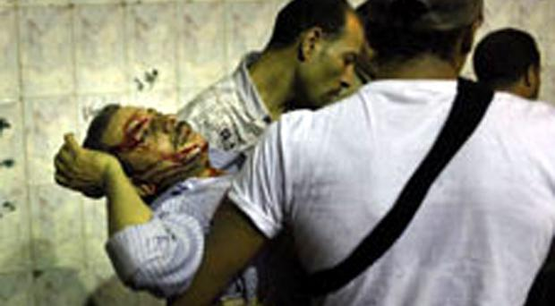 An injured Egyptian Coptic demonstrator during clashes with soldiers in Cairo yesterday