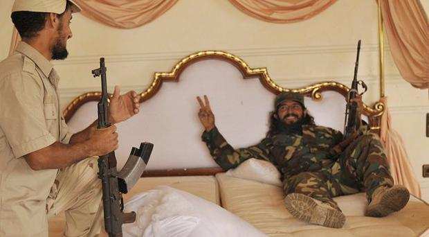Libyan rebels rest in the bed of their country's former leader Muammar Gaddafi in a palace in Sirte(AP)