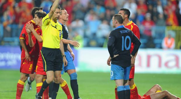 PODGORICA, MONTENEGRO - OCTOBER 07: Wayne Rooney of England is shown the red card after fouling Miodrag Dzudovic of Montenegro during the UEFA EURO 2012 group G qualifier match between Montenegro and England at the Gradski Stadium on October 7, 2011 in Podgorica, Montenegro. (Photo by Michael Regan/Getty Images)