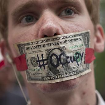A protester stands with a US dollar bill taped over his mouth in Zuccotti Park in New York (AP)