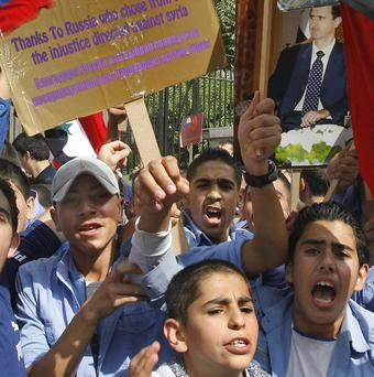 Syrian regime supporters hold placards and shout their backing for President Bashar Assad (AP)