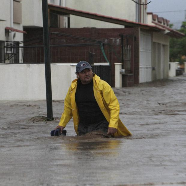A man wades through a street flooded by heavy rains dumped by Hurricane Jova in Villa de las Garzas, Mexico (AP)